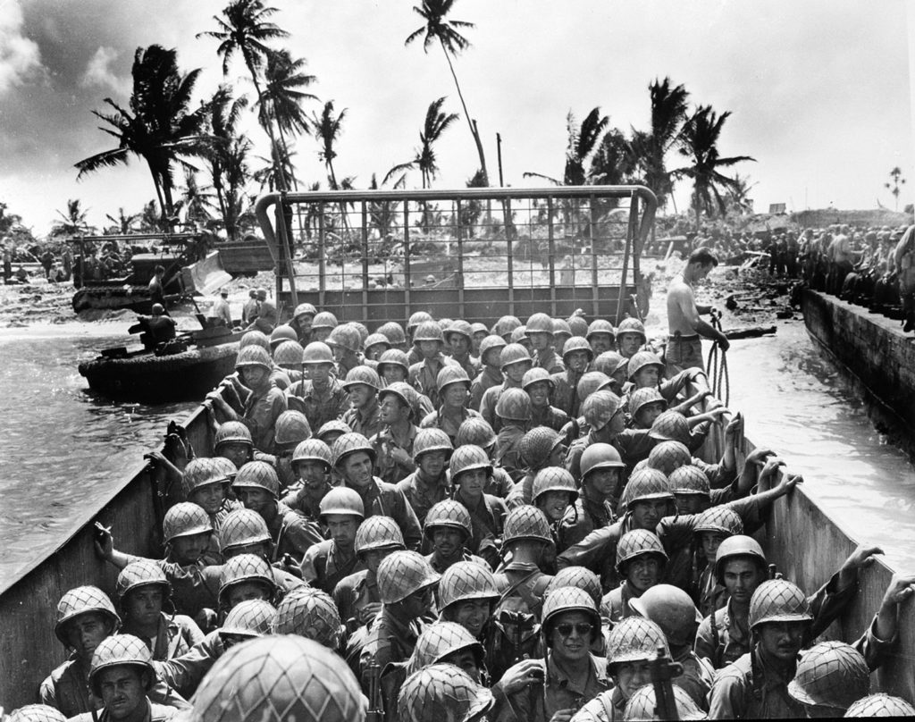 A landing craft packed with Marines approaches an island in the Kwajalein Atoll during the U.S. invasion of the Marshall Islands on March 2, 1944. Ralph Eyde and the 7th Infantry Division also took part in the difficult fighting.